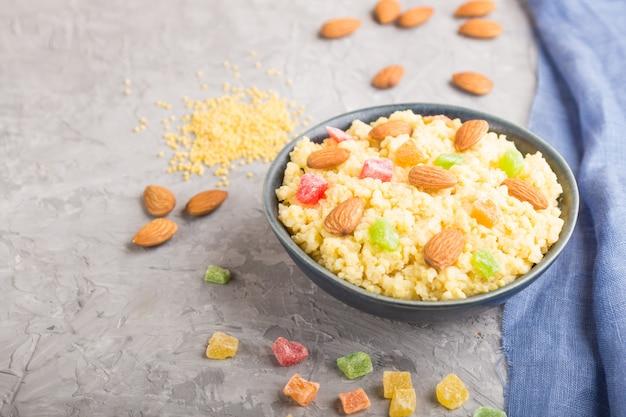 Porridge di miglio con frutta candita e mandorle in ciotola di ceramica blu su uno sfondo di cemento grigio. vista laterale, messa a fuoco selettiva.