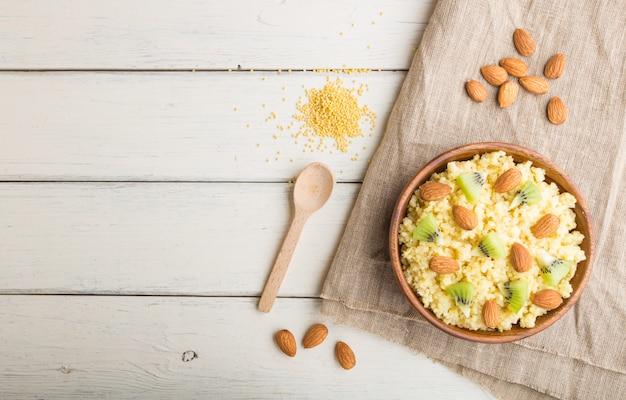 Porridge di miglio con kiwi e mandorle in ciotola di legno su un fondo di legno bianco. vista dall'alto, copia spazio.