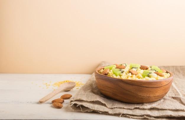 Porridge di miglio con kiwi e mandorle in ciotola di legno su uno sfondo bianco e arancio. vista laterale, copia spazio.