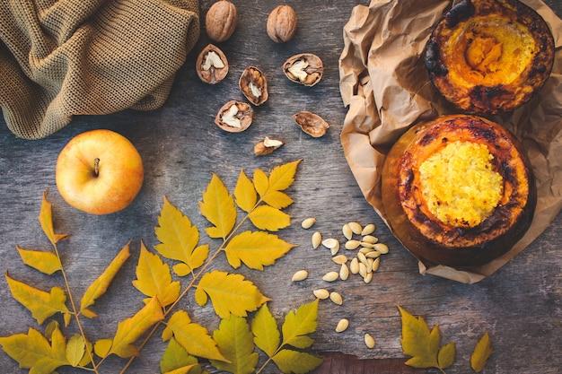Porridge di miglio cotto in zucca, noci, semi, mela, foglie gialle, maglione caldo. immagine tonica. vista dall'alto.