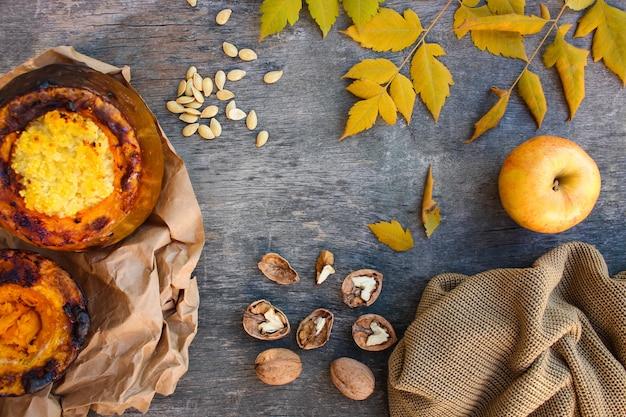 Porridge di miglio cotto in zucca, noci, semi, mela, foglie gialle, maglione caldo su un vecchio legno