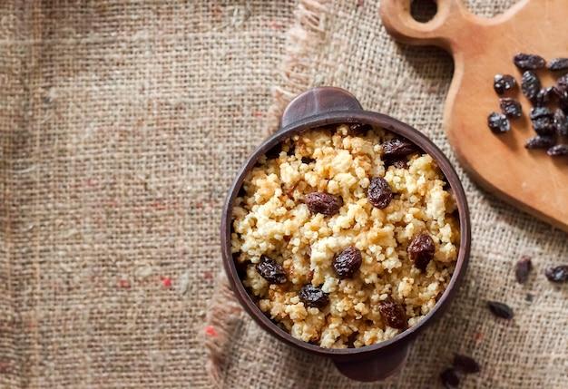 Porridge di miglio dolce con uvetta scura in ciotola rustica in ceramica con noci dentro
