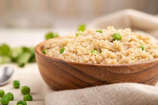 Porridge di quinoa con piselli in ciotola di legno su un fondo di legno bianco. vista laterale, messa a fuoco selettiva.