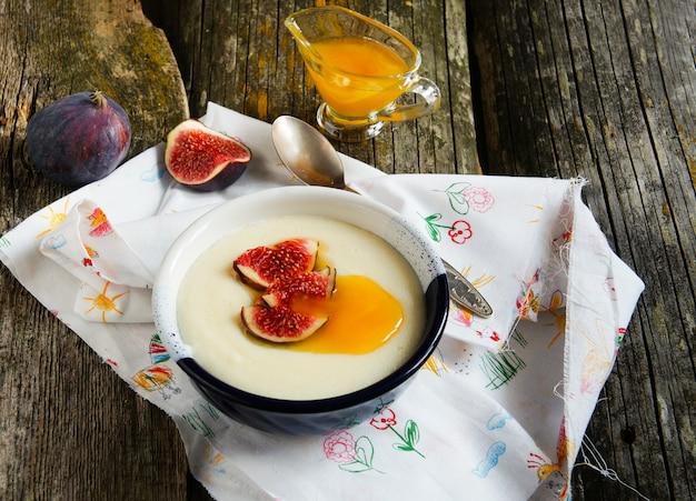 Porridge di semola con fichi e miele o il vecchio bakground di legno