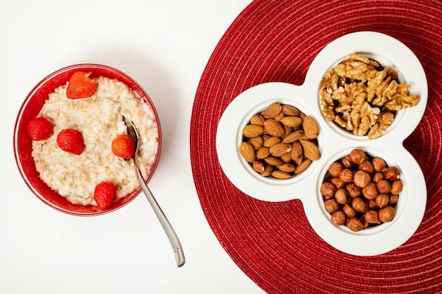 Porridge piatto laici con noci su sfondo chiaro