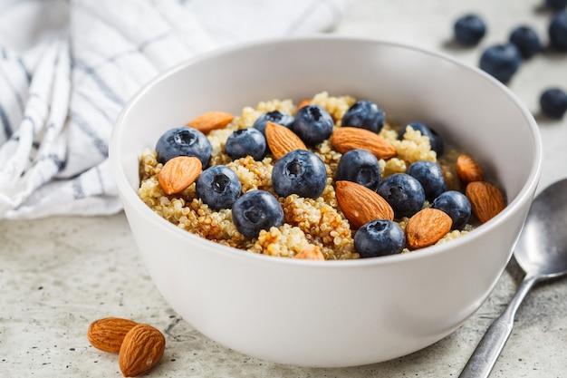Porridge sano della quinoa con i mirtilli e le mandorle con sciroppo in una ciotola grigia. concetto di cibo vegan.