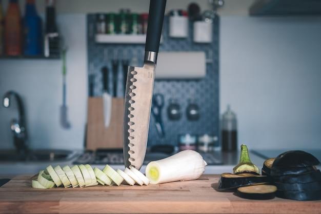 Porro affettato e melanzane con un coltello inchiodato al tagliere e cucina moderna sfocata