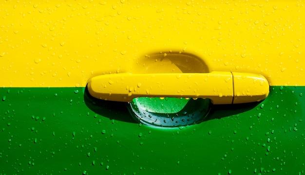 Porta di automobile gialla e verde nella pioggia del giorno - primo piano