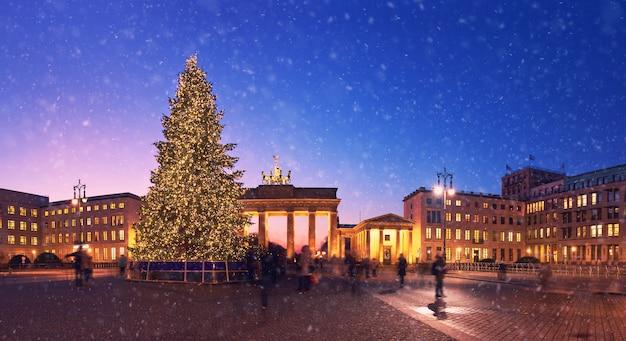 Porta di brandeburgo a berlino con albero di natale e neve che cade la sera
