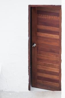 Porta di legno del pannello e della struttura sul fondo bianco della parete, immagine frontale di una porta di legno aperta