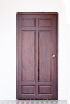 Porta di legno del pannello e della struttura sul fondo bianco della parete, immagine frontale di una porta di legno chiusa