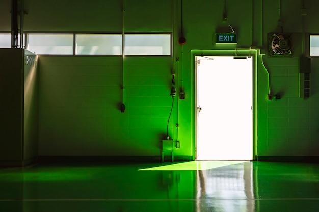 Porta di uscita e area verde del pavimento con la luce del sole.