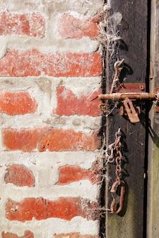 Porta e fondo di legno approssimativi del muro di mattoni