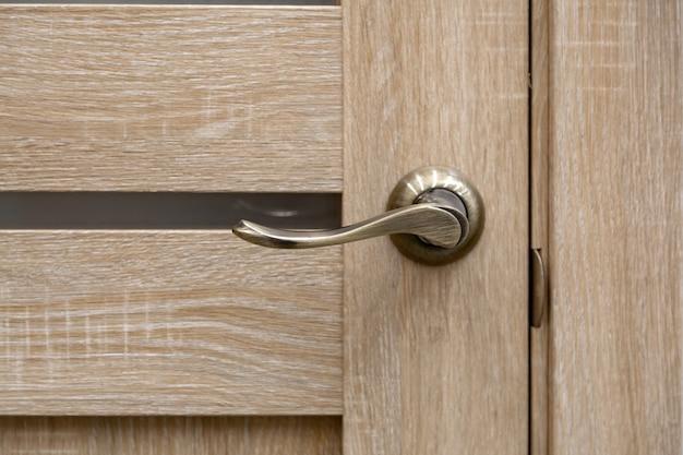 Porta in acciaio, finiture in legno. diverse serrature e una maniglia. porta dell'hotel con manopola moderna