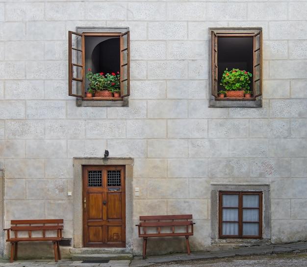 Porta in legno sul muro di blocchi di cemento grigio vuoto con apertura superiore a due finestre decorate con fiore