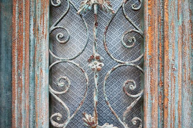 Porta incorniciata in legno verniciato scuro squallido con grate in metallo decorato antico trame a reticolo modellato. dettagli architettonici della porta d'epoca del vecchio edificio