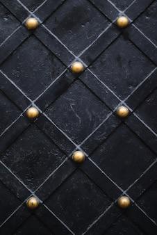 Porta nera con vecchi elementi di struttura metallica dorata