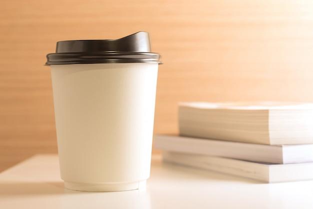 Porta via la tazza di caffè di carta sul fondo di legno del tavolo bianco