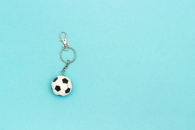 Portachiavi con pallone da calcio o calcio su sfondo blu in stile minimal. vista dall'alto copia spazio