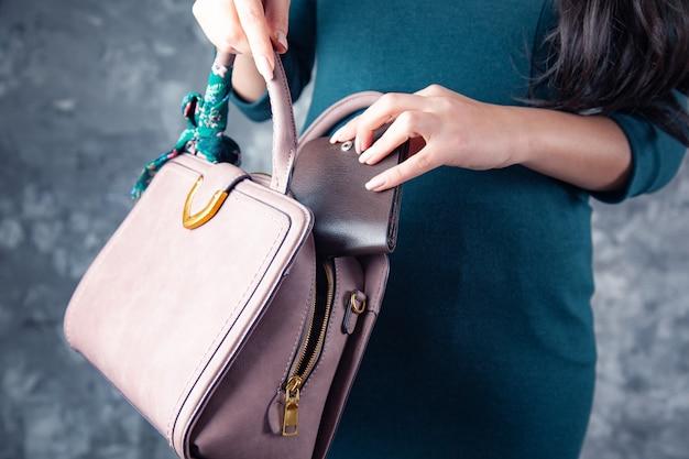 Portafoglio a mano donna con borsa su sfondo scuro