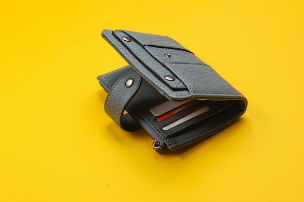 Portafoglio aperto in pelle con carte di credito su fondo giallo