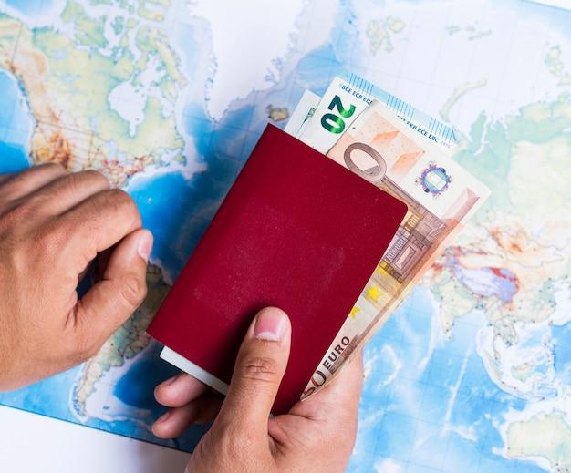 Portafoglio chiuso con euro e mappa del mondo