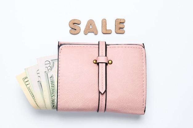 Portafoglio d'avanguardia con le banconote in dollari su superficie bianca con la vendita del testo.