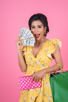 Portafoglio e sacchetti della spesa della tenuta della mano della giovane donna di modo