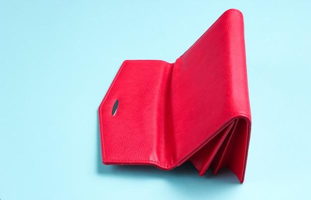 Portafoglio in pelle rossa rovesciata sulla superficie blu