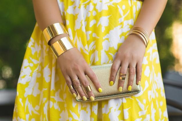 Portafoglio irriconoscibile della tenuta della donna in sue mani. mani del `s della signora che indossano gli anelli e gli accessori. ragazza in abito giallo