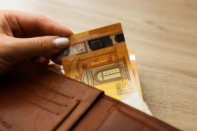 Portafoglio pieno di banconote in euro sul backround in legno