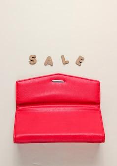 Portafoglio rosso alla moda su una superficie beige con scritta saldi.
