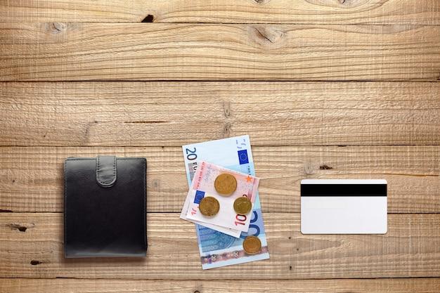 Portafoglio, soldi e carta di plastica su legno