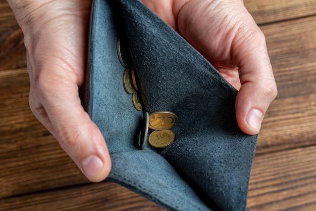 Portafoglio vuoto e mano che tengono poche monete