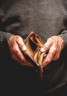 Portafoglio vuoto nelle mani di un uomo anziano