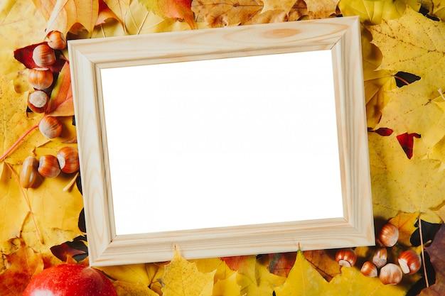 Portafoto in legno bianco con nocciole su foglie di acero colorate.