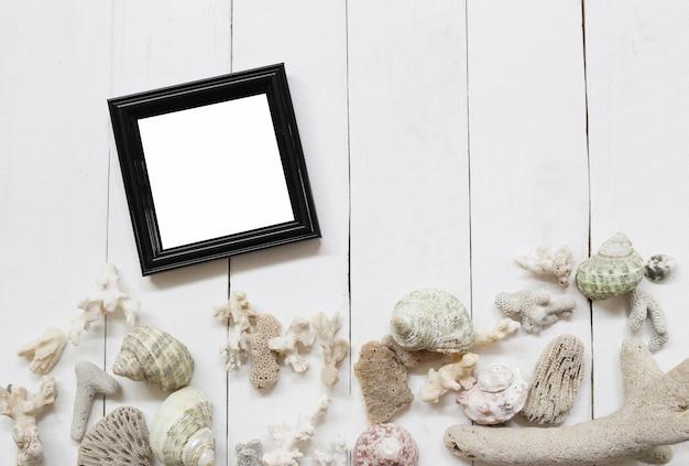 Portafoto in legno nero su un pavimento in legno bianco e conchiglie e barriere coralline.