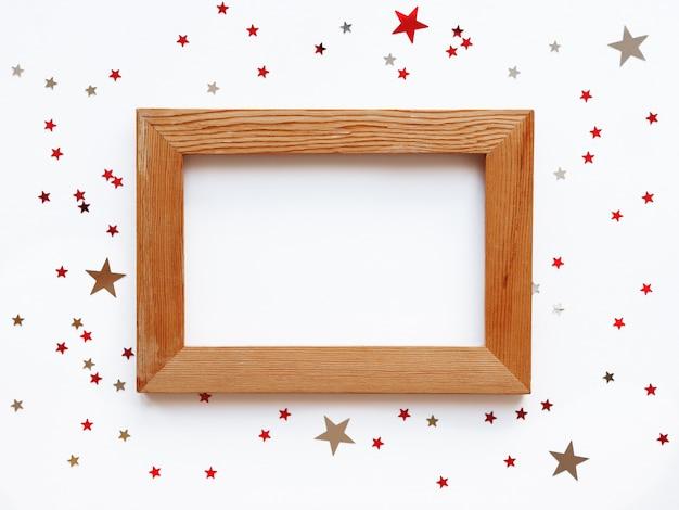 Portafoto in legno squallido su sfondo bianco con coriandoli di stelle di scattering