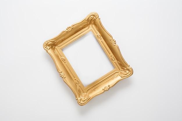 Portafoto in oro in stile vintage, situato su un muro bianco. una cornice concettuale per la registrazione di certificati, premi e diplomi o un design elegante di qualsiasi argomento.