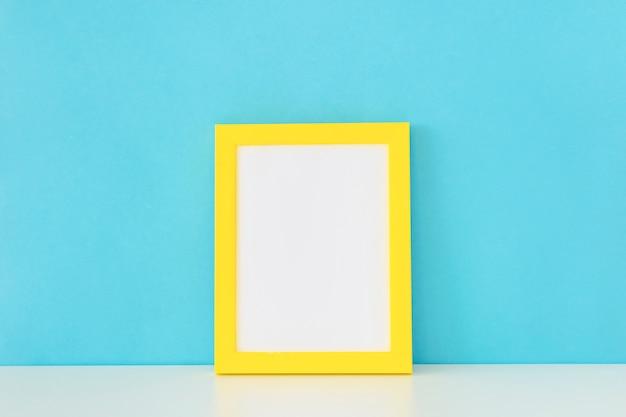 Portafoto vuoto giallo davanti alla parete blu