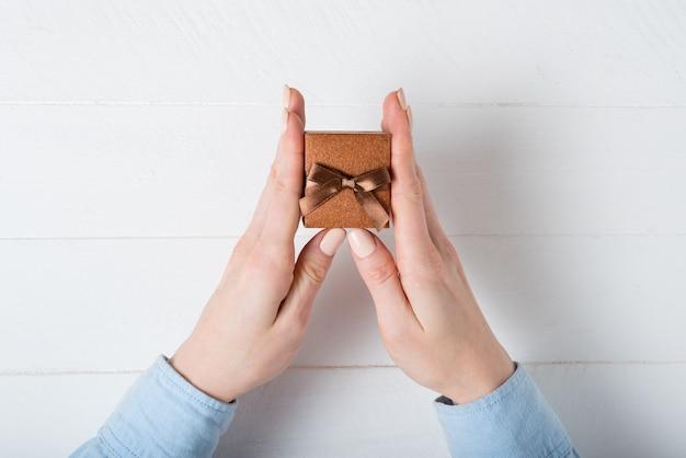 Portagioie marrone in mani femminili. presente