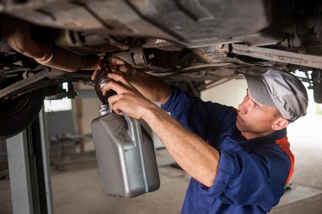 Portait del meccanico di automobile che scarica l'olio per motori sotto l'automobile sollevata