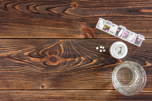 Portapillole medico con compresse e bicchiere d'acqua