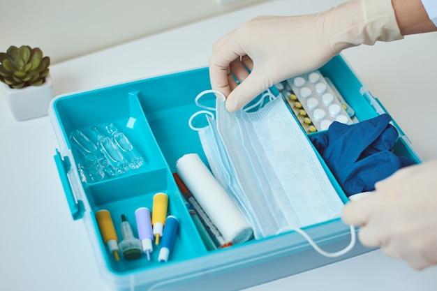Portare i guanti con la maschera protettiva in midicina dal kit di pronto soccorso. scatola della medicina domestica con oggetti medici. concetto di protezione da virus.