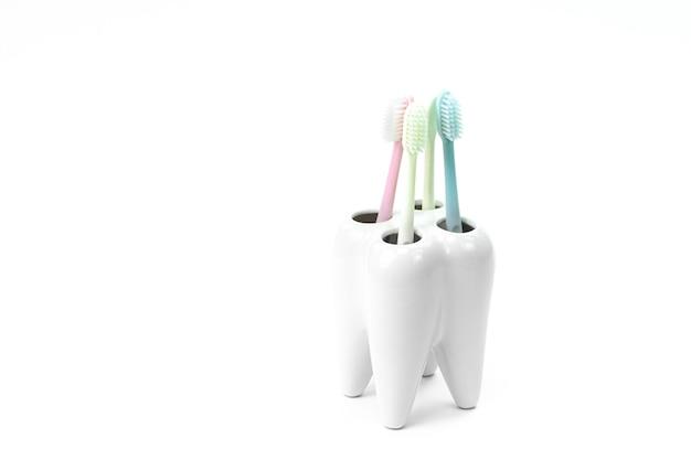 Portaspazzolino a forma di dente primario con spazzolini colorati