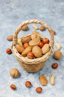 Portata del cestello in vari tipi di noci con gusci, arachidi, mandorle, nocciole e noci sulla superficie del calcestruzzo