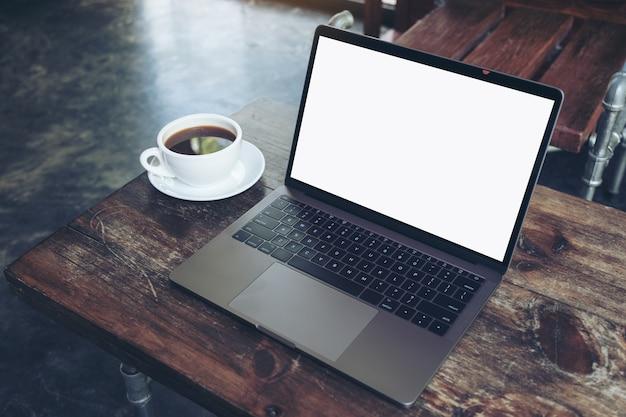 Portatile con schermo desktop bianco vuoto e tazza di caffè sul tavolo di legno nel caffè moderno