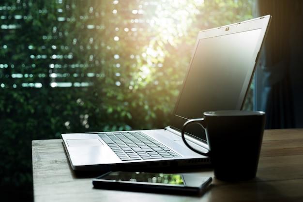 Portatile con schermo vuoto, smartphone e tazza sul tavolo di legno vicino alla finestra