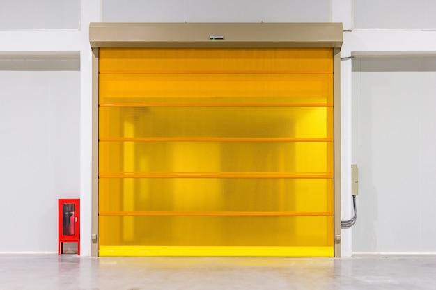 Portello dell'otturatore del rullo e pavimento di calcestruzzo all'interno della costruzione della fabbrica per fondo industriale.