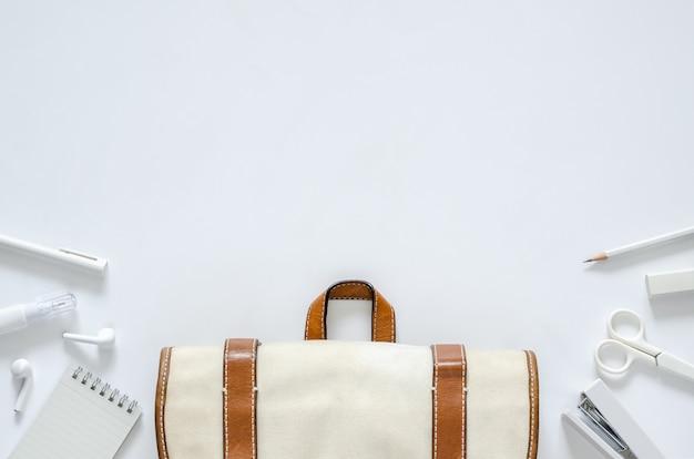 Porti la borsa con i rifornimenti della cancelleria dell'ufficio e della scuola su fondo bianco per di nuovo al concetto della scuola.